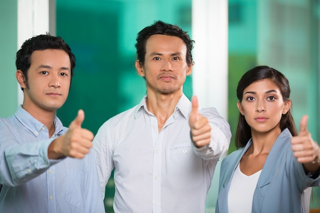 Three confident business people showing thumbs up