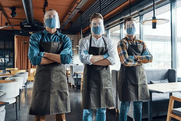 Трое уверенных в себе мужчин-официантов в защитной спецодежде, скрестив руки и