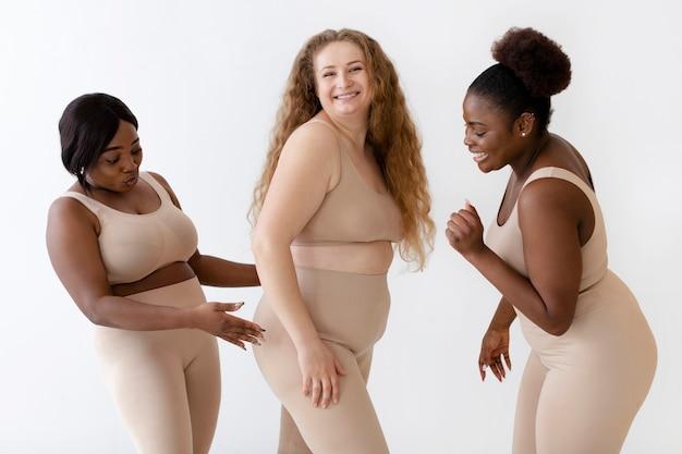 Три уверенных в себе женщины позируют вместе в корректоре тела