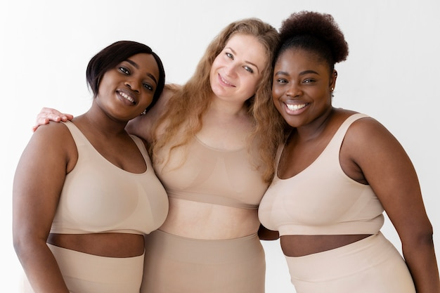 Tre donne sicure in posa mentre indossa un body shaper