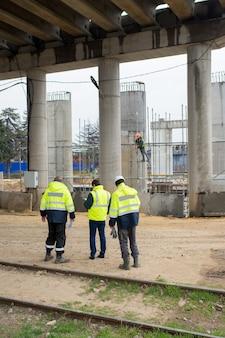 3 명의 건설 감독이 건설 현장에서 협의합니다.