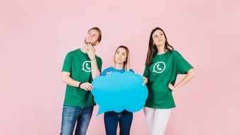 Three contemplated young friends holding blue speech bubble