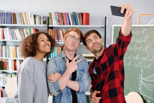 Трое современных товарищей по команде позируют для селфи перед смартфоном в библиотеке или классе