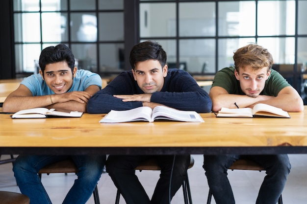 Three content students lying on desk and looking at camera