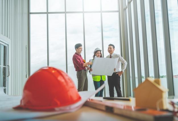 세 명의 계약자 팀이 종이 도면을 작성하여 엔지니어 테이블 맨 끝에있는 건물 계획에 대해 브레인 스토밍하고 있습니다.