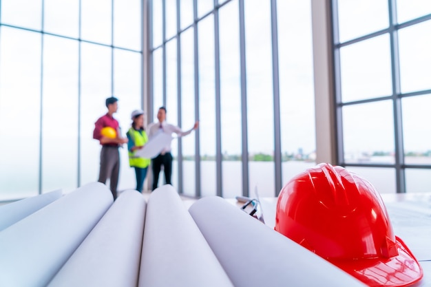 세 명의 계약자 팀이 종이 도면을 작성하면서 엔지니어 테이블의 맨 끝에서 논의하고 있습니다.