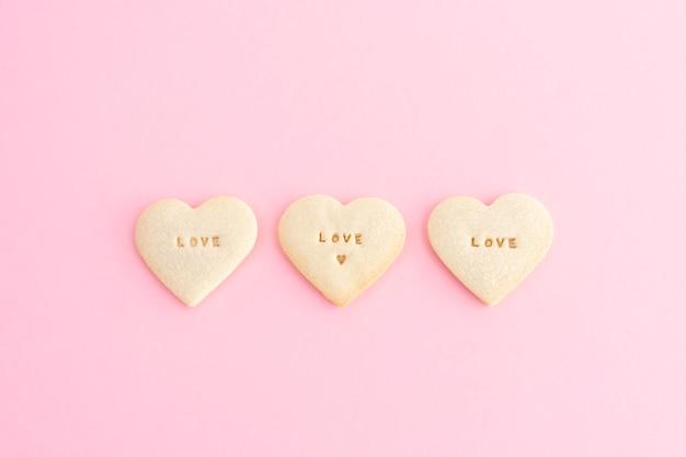 Три печенья в форме сердца и слова любовь на розовом фоне. день святого валентина, день матери, юбилей. скопируйте пространство. вид сверху.