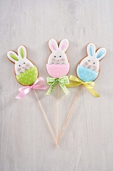 Three cookies in the shape of cute bunny on stick
