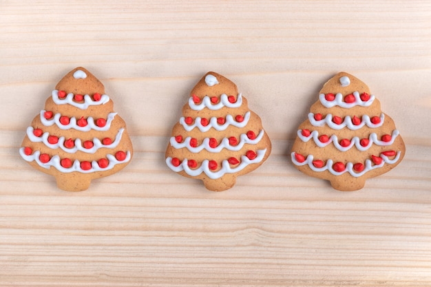 Three cookies shaped christmas tree on a wooden background