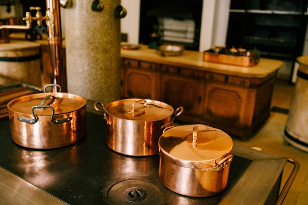 Three copper pots on the stove against the background of a long wooden table in a vintage dining room