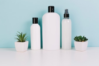 Three cosmetics bottles near plants