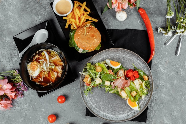 Three-course business lunch. lunch with burger asian ramen noodles and caesar salad.