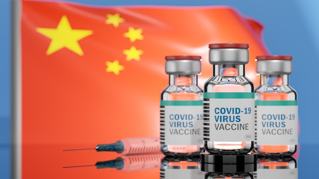 Three covid-19 virus vaccine bottles and  a syringe with a needle on a flag of china surface