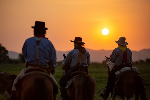 Three cowboys riding horse against sunset
