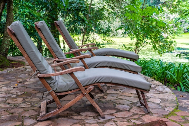 Three cozy sun loungers on the tropical garden terrace near lake