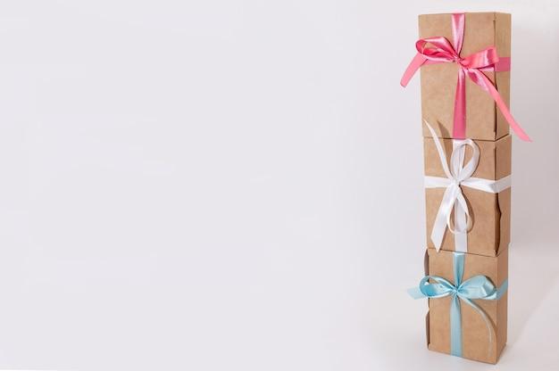Три подарочные коробки, перевязанные белыми, розовыми и синими атласными лентами, стоят друг на друге на белом фоне с местом для подписи.