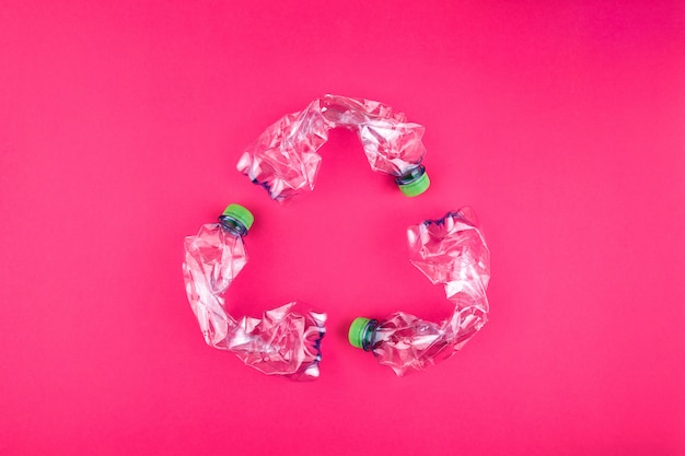 Three crashed plastic bottles on bright fresh pink background form resycling sign