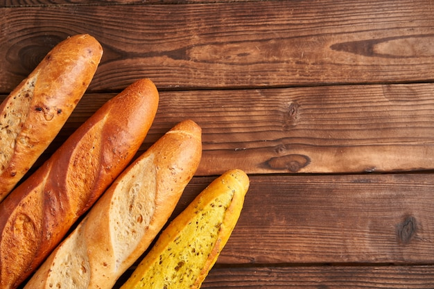 Three crispy french baguettes lie on an old wooden table with free space