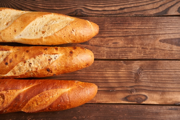 Three crispy french baguettes lie on an old wooden table