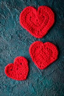 暗い表面に3つのかぎ針編みのバレンタインハート。