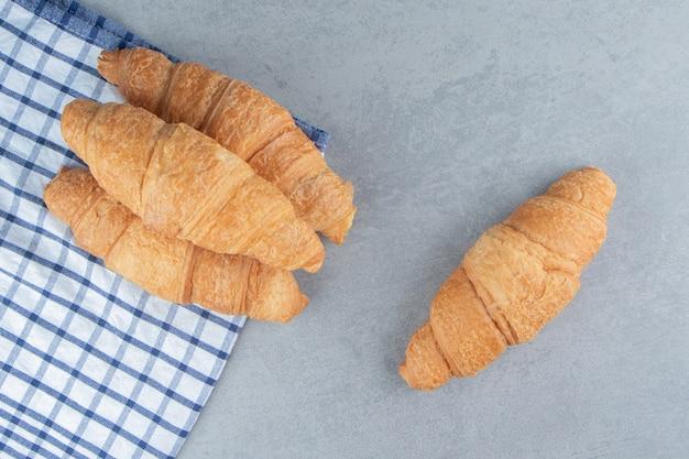 Tre croissant impilati sull'asciugamano con un croissant sullo sfondo di marmo. foto di alta qualità