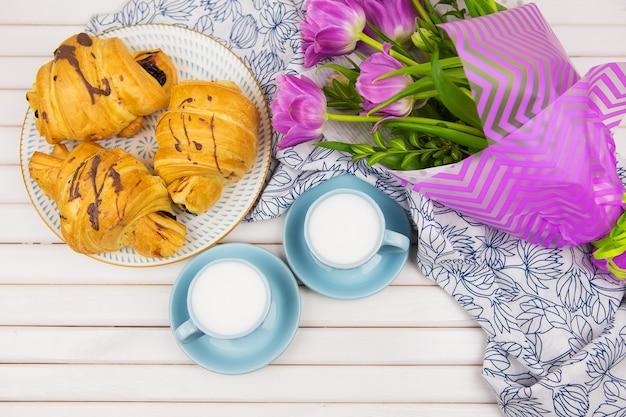 クロワッサン3杯、テーブルにコーヒー2杯、美しいチューリップの花束