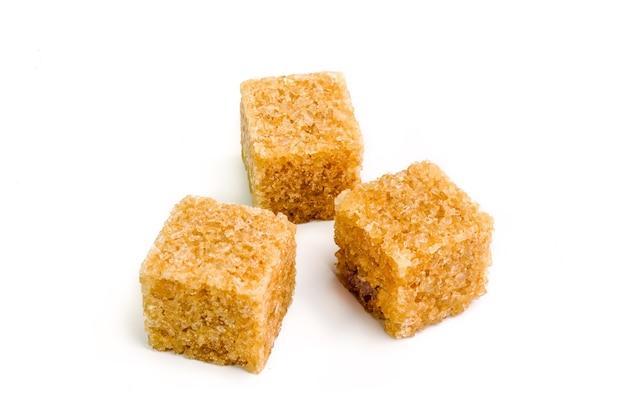 Три кубика коричневого сахара с тенью на белом.