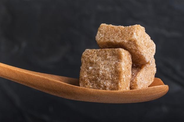 나무로되는 숟가락에 으깬 지팡이 설탕 3 개