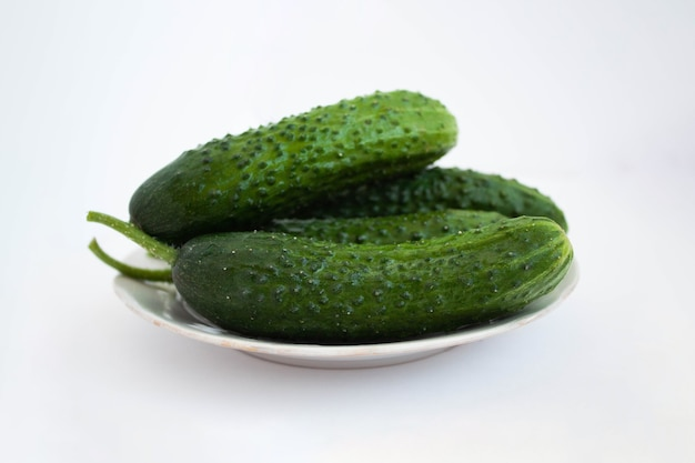Three cucumbers are lying on a plate on a white background