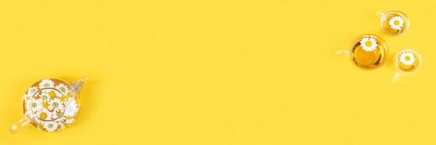 Три чашки чая и прозрачный чайник с цветами ромашки на желтом фоне