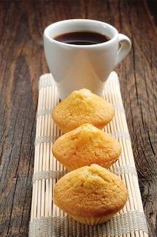 木製のテーブルに3つのカップケーキとコーヒーのカップ