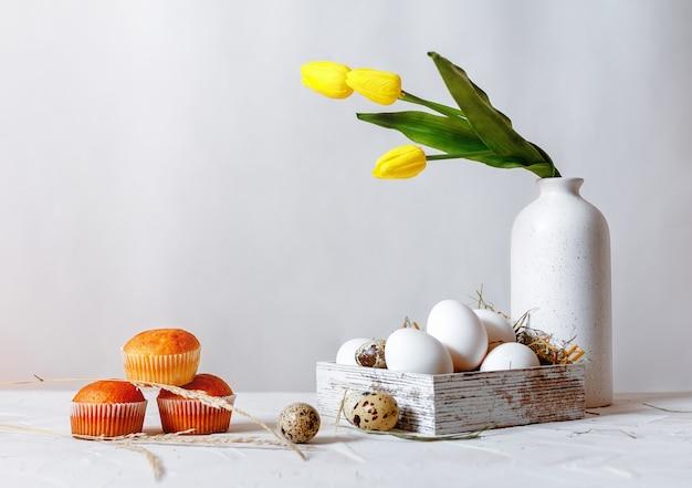 가벼운 테이블에 세 컵 케이크입니다. 회색에 짚이 있는 나무 상자에 흰색 닭고기 달걀과 메추라기 알