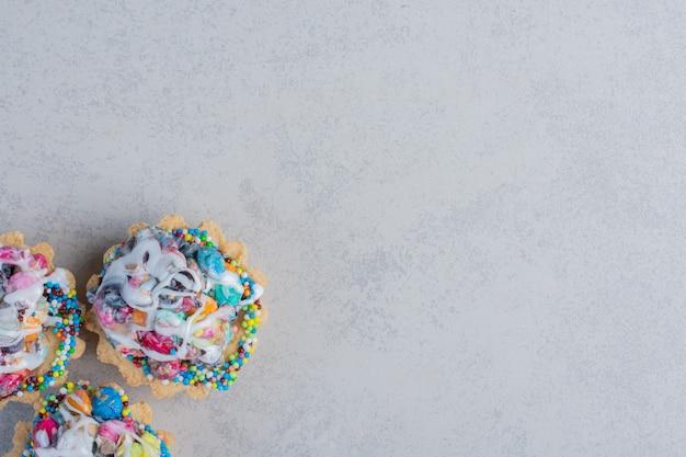Tre cupcakes con condimenti di caramelle impacchettati insieme su una superficie di marmo