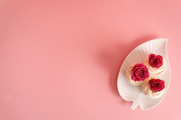 ピンクの背景のコピースペースの白いプレートの上部にバラのつぼみを持つ3つのカップケーキ