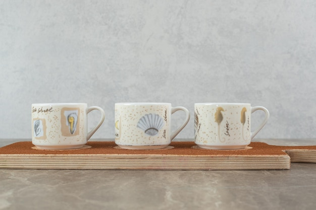 Three cups of coffee on wooden board.
