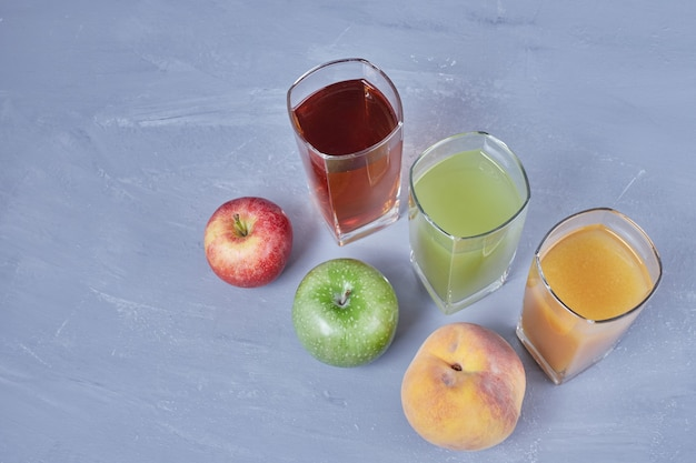 Three cups of different fruit juices.