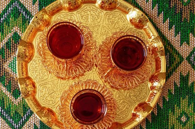 Три чашки черного чая на золотом восточном подносе