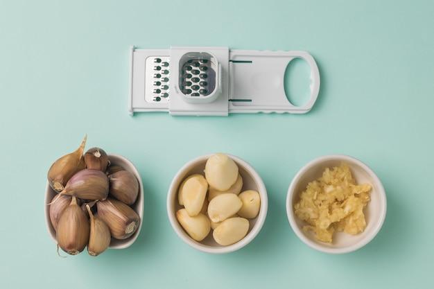 青い表面にニンニクとおろし金の種類が異なる3つのカップ。キッチンに人気のスパイス。