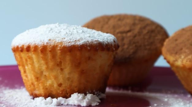 파란색 배경 클로즈업에 분홍색 접시에 초콜릿과 착빙 설탕을 뿌린 세 개의 두부 케이크. 디저트, 작은 컵케이크. 공기가 잘 통하는 질감의 흰색 구운 쿠키입니다.