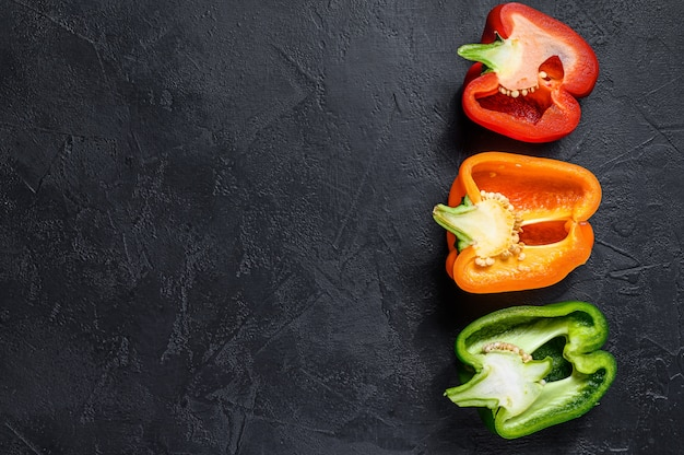 Three cut orange, green and red sweet peppers.