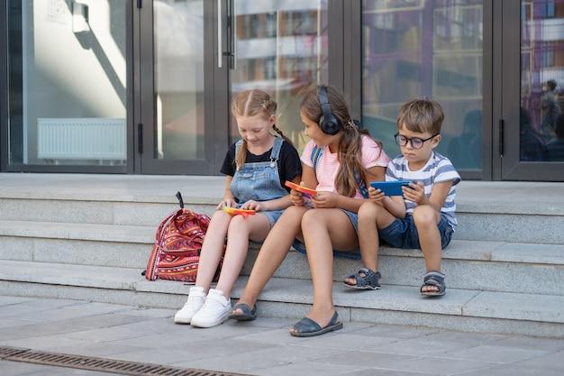 헤드폰과 배낭을 메고 있는 귀여운 백인 아이들 3명이 앉아서 전화를 합니다. 팝핏을 재생합니다. 방학. 얼간이. 학교 개념으로 돌아가기.