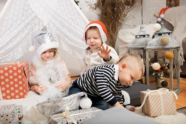 장식 된 집에서 선물 상자 사이에서 놀고 크리스마스 모자를 쓰고 세 귀여운 어린이 아이. 메리 크리스마스와 해피 홀리데이!