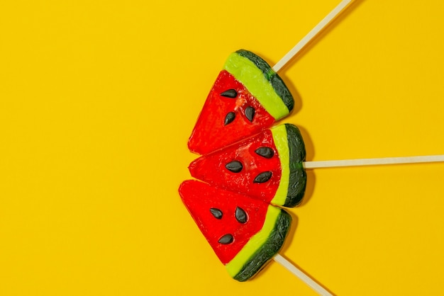 Three cute colorful lollipops look like watermelon on a yellow background