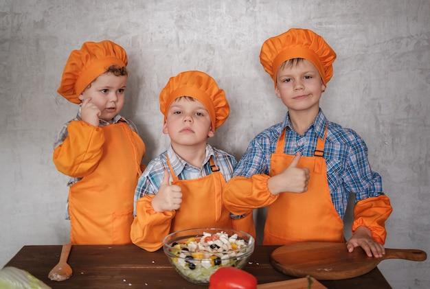 オレンジ色の衣装を着た3人のかわいいヨーロッパの男の子が野菜のサラダを準備します。家族の夕食を作る