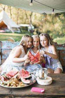3つのかわいい幸せな笑顔の女の子、姉妹、悪魔、ヴィンテージの木製ベンチのテーブルに座って、屋外でスイカを食べる