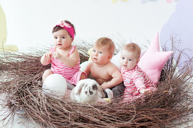 Three cute little babies and rabbit with easter eggs sitting in huge nest