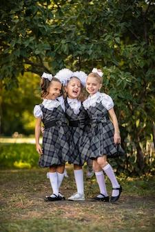 校庭でポーズをとって尾と白の弓の制服姿の3人のかわいい若い女の子