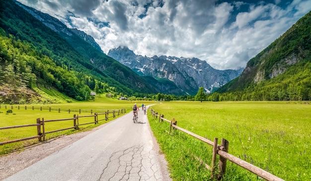 Три велосипедиста по дороге в гору, люди на велосипедах с зелеными полями