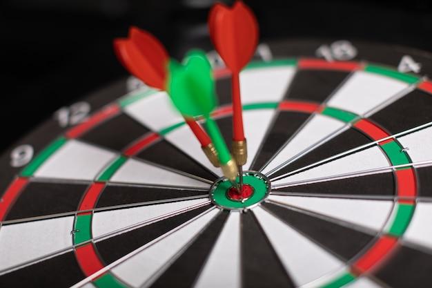 Three darts hit red target close-up