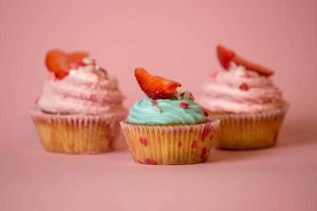 Три украшенных кекса с голубым и розовым сливочным кремом